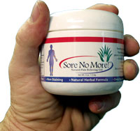 Hand holding a jar of Sore No More topical pain relief gel